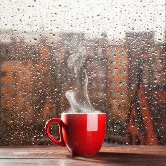 Обои Кружка с кофе стоит на окне покрытом капельками дождя из окна открывается вид на дома