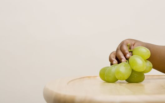 Обои Маленькая детская рука держит зеленый виноград
