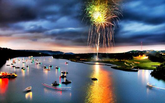 Обои Фейерверк на берегу реки, усыпанной лодками, на фоне небо с темными тучами на закате