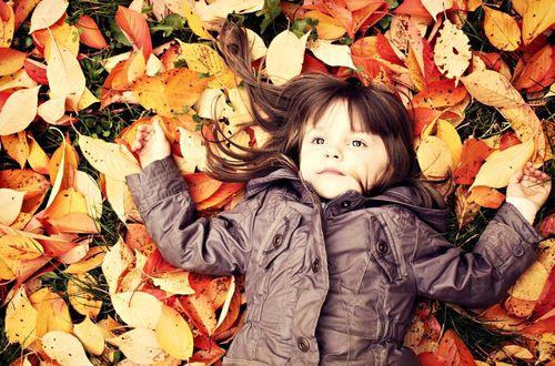 Обои Маленькая девочка лежит на осенних листьях