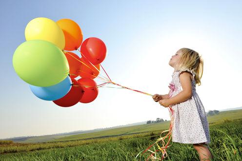 Обои Маленькая девочка стоит в поле и держит в руках воздушные шары на фоне неба