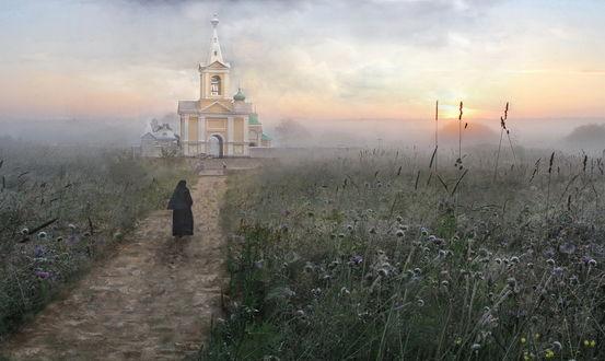 Обои Восходящее из-за линии горизонта солнце на утреннем небосклоне с темными тучами и легкой туманной дымкой осветило каменную церковь и женщину-священнослужителя, идущую по мощеной дороге с растущими по обочинам колючками, автор Людмила