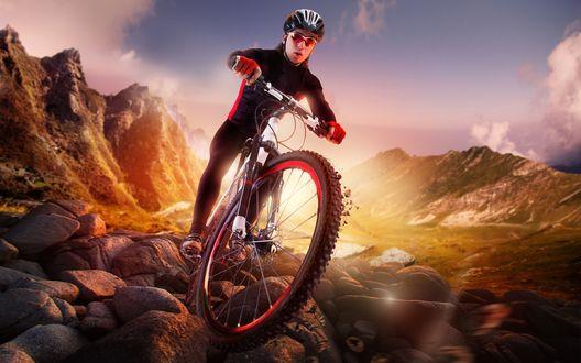 Обои Спотрсмен в экипировке едет на горном велосипеде по камням, среди гор