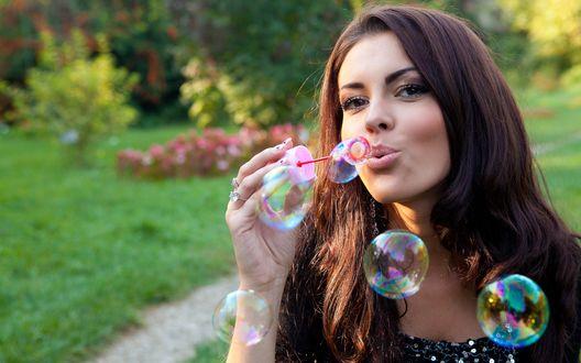Обои Девушка сидя на лужайке, пускает мыльные пузыри