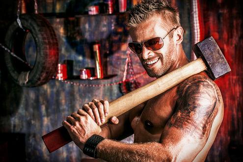 Обои Обнаженный до пояса мужчина в солнцезащитных очках с тату на предплечье, стоит в гараже улыбаясь и держит в руках положив на плечо, большую кувалду