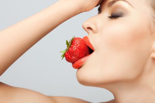Обои Девушка закрыв глаза и подняв руку к голове, держит в губах ягоду клубники
