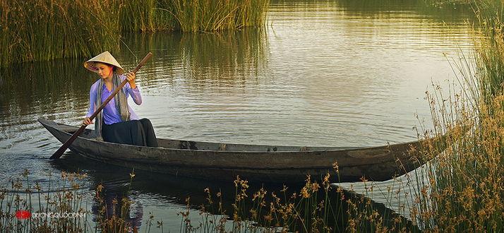на лодке с веслом в руках