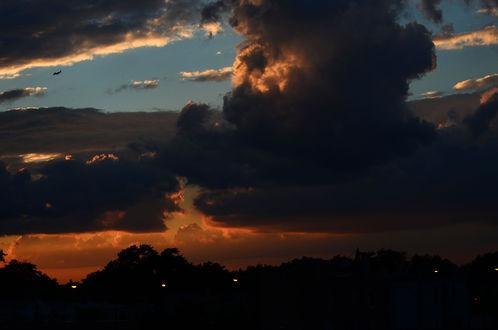 Обои Мрачное ночное облачное небо с летящим самолетом