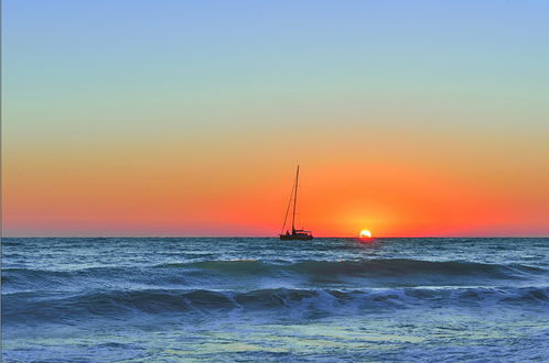 Обои Рыбацкий баркас, плывущий по морю на фоне заходящего за линию горизонта солнца на вечернем небосклоне, автор Сергей Бридихин