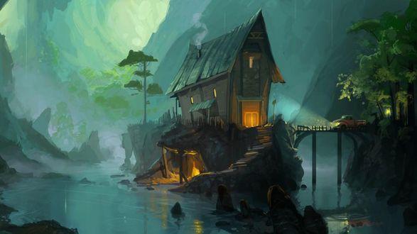 Обои Деревянный домик с мансардой, с вьющимся из трубы дымком, стоящий на горном утесе на озере в окружении скал с островерхими вершинами, легковым автомобилем с включенными фарами, стоящим на мосту, идущим к дому