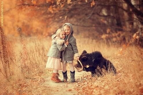 Обои Две светловолосые, улыбающиеся девочки, стоящие в обнимку на песчаной дорожке, усыпанной осенними листьями, одна из них держит в руках плетеную корзинку в которую засунул свой нос любопытный медвежонок, автор Елена Карнеева