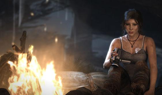 Обои Грустная Лара Крофт / Lara Croft с камерой в руках сидит у костра в пещере из игры Tomb Raider / Расхитительница гробниц