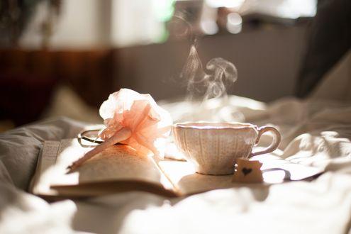Обои Утром на постели лежит раскрытая книга, на ней лежит авторучка в виде розы и стоит чашка дымящегося питья и печенька с сердечком