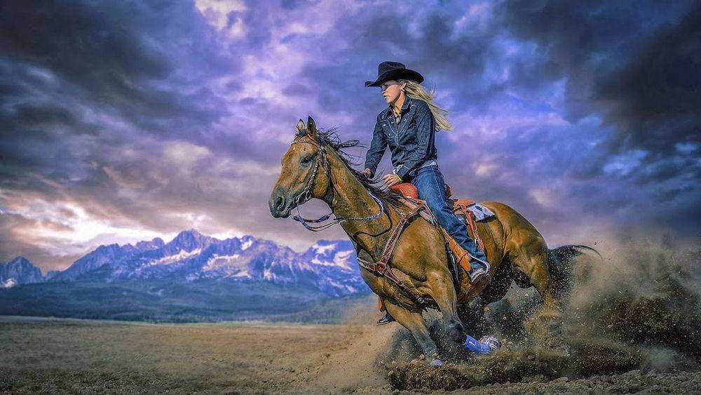 Обои для рабочего стола Девушка в шляпе и джинсовом костюме, скачет на лошади, на фоне гор