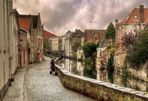 Обои Женщина, стоящая на мощеной набережной неширокого, городского канала на фоне серого, пасмурного неба и парящими в небе птицами, автор Александр Атоян