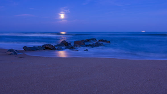 Обои Ночной пляж с камнями в воде моря, над которым светит полная Луна, отражаясь в воде