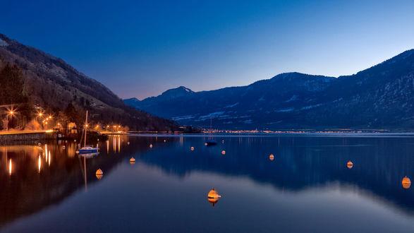 Обои Горное озеро на фоне ночного неба, ярко освещенной набережной на берегу, зажженных фонариков, плавающих по поверхности воды