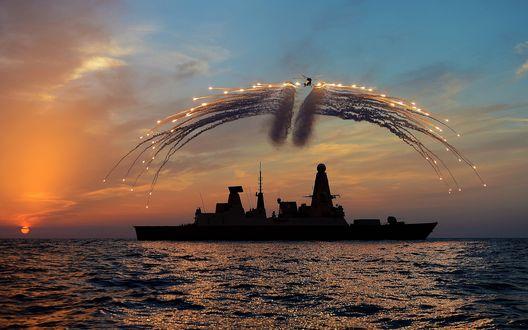 Обои Вертолет взлетевший с военного корабля, выстреливает в небе световые ракеты