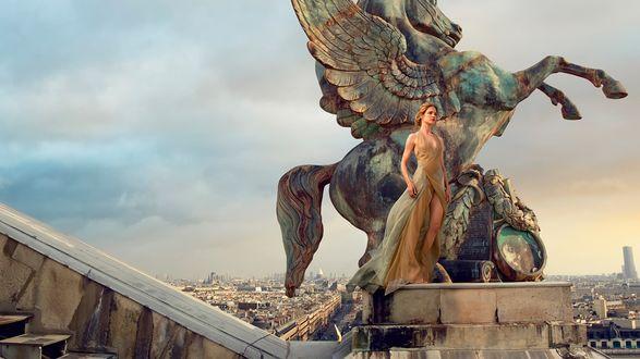 Обои Фотомодель Наталья Водянова стоит в полуобнаженном виде у статуи лошади с крыльями / Пегаса / на площадке, на фоне города