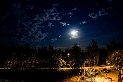 Обои Автомобиль, стоящий на дороге в освещенном пространстве на фоне ночного неба с небольшой облачностью и ярко светящейся луной, автор Богдан Королев