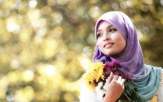 Обои Девушка в восточном наряде на размытом фоне улыбается и держит в руке букетик цветов