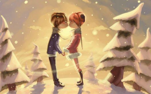 Обои Целующиеся парень и девушка, стоящие между заснеженных деревьев в снежной круговерти