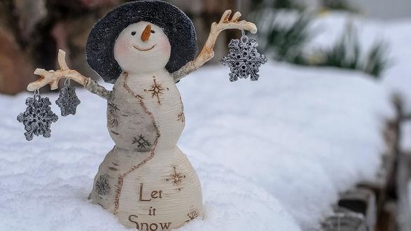 Обои Керамический снеговик со снежинками стоит на снегу в шляпе