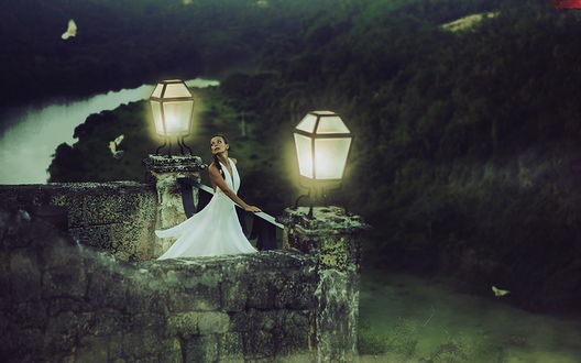 Обои Темноволосая девушка в белом платье, стоящая на каменной, обзорной площадке над протекающей внизу рекой в окружении горящих фонарей и парящих в небе птиц, автор Andrew Lucas