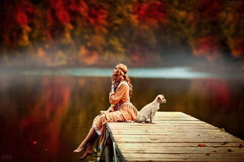 Обои Рыжеволосая, босоногая девушка, сидящая на деревянном мостике с осенними листьями, расположенном у берега озера, рядом с ней сидит с домашняя собака, автор Светлана Беляева