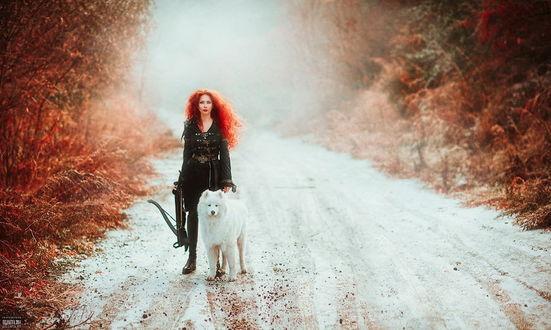 Обои Стройная девушка с распущенными, рыжими волосами, держащая в руке арбалет, идущая по дороге со свежевыпавшим снегом, обочины которой усыпаны осенними листьями, рядом с ней идет белая, пушистая собака, автор Светлана Беляева