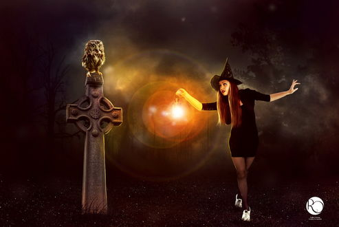 Обои Рыжеволосая девушка в островерхой черной шляпе, держащая в руке ярко горящий фонарь, стоящая у каменного надгробья в виде креста с сидящей на нем совой, автор Reginasamargo