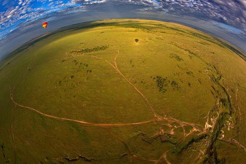 Обои Красный, воздушный шар, парящий в воздухе над землей на фоне пасмурного небосклона, фотография выполнена при помощи широкоугольного объектива автором Александром Перовым