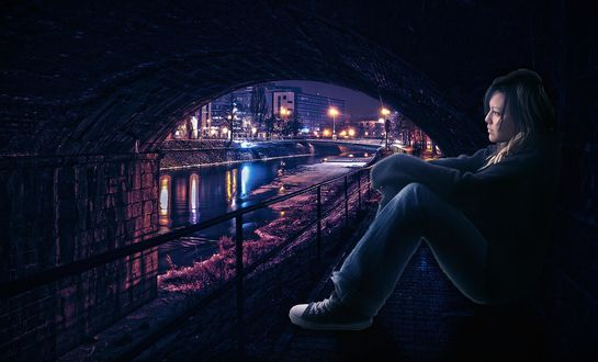 Обои Девушка сидит под каменным мостом у воды канала с виднеющимися вдали мостами и ночным городом с горящими фонарями