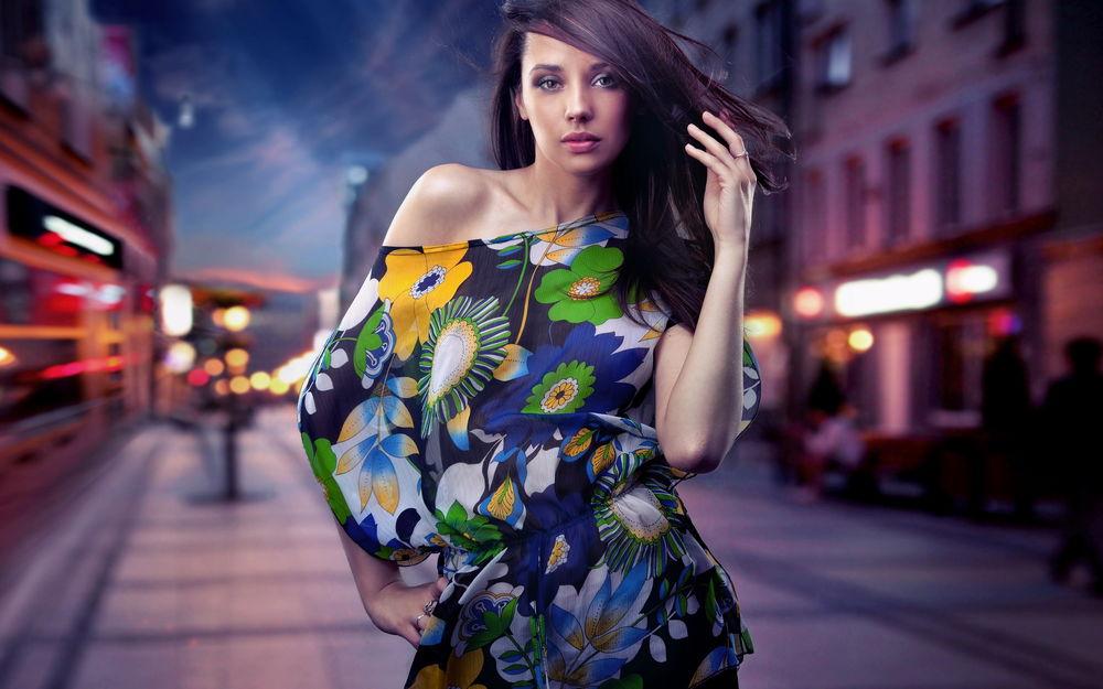 Обои для рабочего стола Девушка в цветастой блузке, уперев одну руку в бок, а другой поправляя волосы стоит посреди улицы с размытым фоном