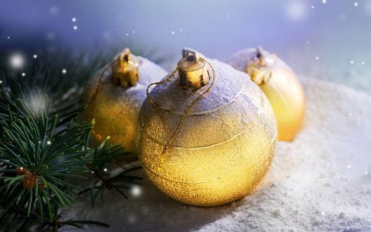 Обои Золотистые елочные шары лежат на снегу