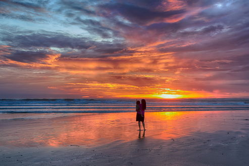 Обои Женщина, держащая на руках свою дочь, стоящие на песчаном, морском побережье на фоне яркого, солнечного заката на вечернем небосклоне с разноцветными облаками, автор Людмила