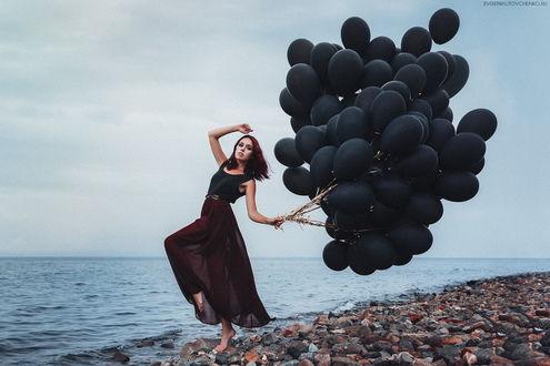 Обои Босоногая девушка, стоящая на морском побережье, держащая в руке огромную связку черных, воздушных шариков, автор Евгения Литовченко