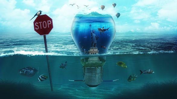 Обои Стеклянная лампочка, заполненная водой со стоящей в ней американской Статуей Свободы с плавающими вокруг нее акулой и другими рыбами, затопленной в море невдалеке от знака STOP / СТОП с сидящей на нем птицей на фоне парящих в воздухе воздушных шаров