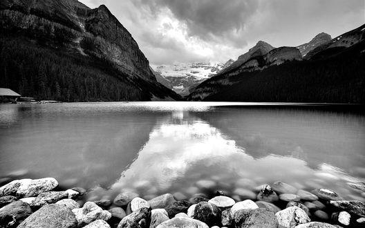 Обои Озеро окруженное высокими горами, поросшими лесом с отражением неба с облаками на поверхности воды