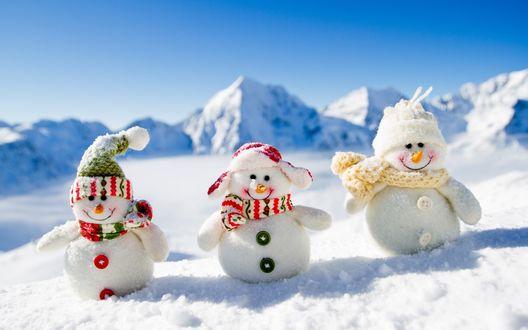 Обои Три игрушечных снеговичка стоят на снегу на фоне горы и неба