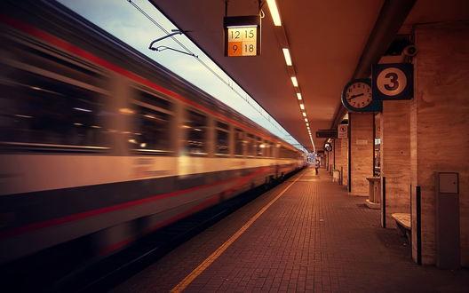 Обои Пассажирский поезд, отходящий от перрона железнодорожного вокзала на фоне светящихся указателей и ночного неба