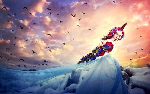 Обои Девушка в платье и головном уборе из цветов сидит на заснеженном камне, придерживая рукой развевающуюся вуаль, в небе летает множество птиц