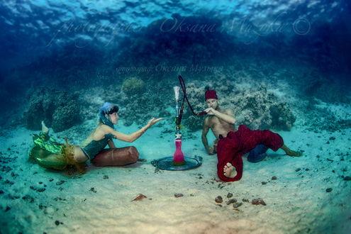 Обои Мужчина и женщина, лежащие на песчаном, морском дне с наслаждением курят кальян, автор Оксана Музыка
