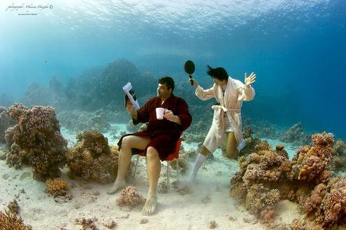 Обои Черноволосый мужчина, сидящий на стуле с чашкой кофе, читающий книгу, находящийся на морском дне, сзади него стоит грозная жена со сковородой в руке, автор Оксана Музыка
