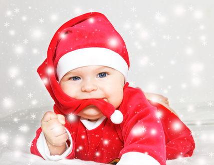 Обои Малыш одетый в костюм Санта-Клауса взял в рот край шапочки, одетой на голову