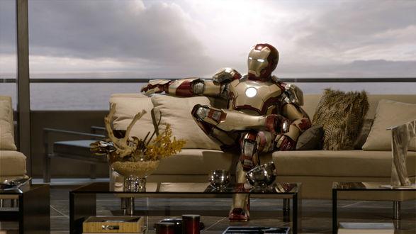 Обои Тони Старк в костюме железного человека присел отдохнуть на диван в своем шикарном доме в Малибу, закинув ногу на ногу / актер Роберт Дауни Младший в фильме Железный человек