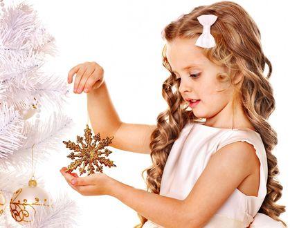 Обои Девочка с красивыми вьющимися волосами, белым бантом на голове стоит возле новогодней елки с игрушками и готовится повесить игрушку в виде большой золотой снежинки