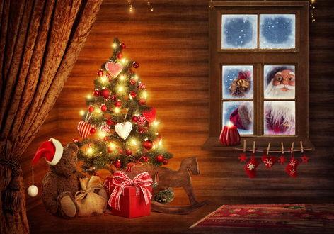 Обои Дед Мороз с подарками заглядывает через заиндевевшее окно в комнату. где стоит новогодняя елка с игрушками и огнями, под которой сидит игрушечный мишка и лежат другие подарки