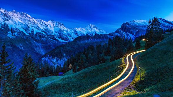 Обои Извилистая горная дорога с яркими, световыми полосами, проходящая на фоне горного образования со снежными вершинами на фоне вечернего небосклона с темно-синими облаками