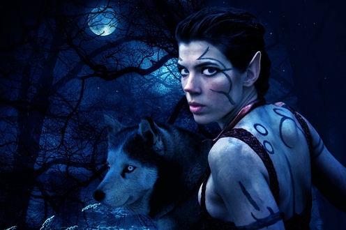 Обои Темноволосая девушка-эльфийка с разрисованным лицом и телом, стоящая рядом с волком на фоне ночного неба с полной луной